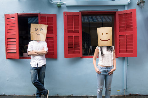 Unknown male and female with their faces covered with paper bags, standing in front of blue colored wall and red window sill