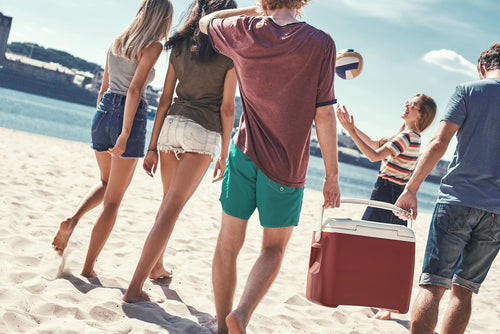 Young group of friends walking on a beach and having fun
