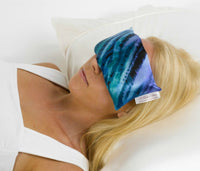 A attractive blonde haired girl lying on a white bedroom pillow with a blue pattern satin eye pillow covering her eyes.