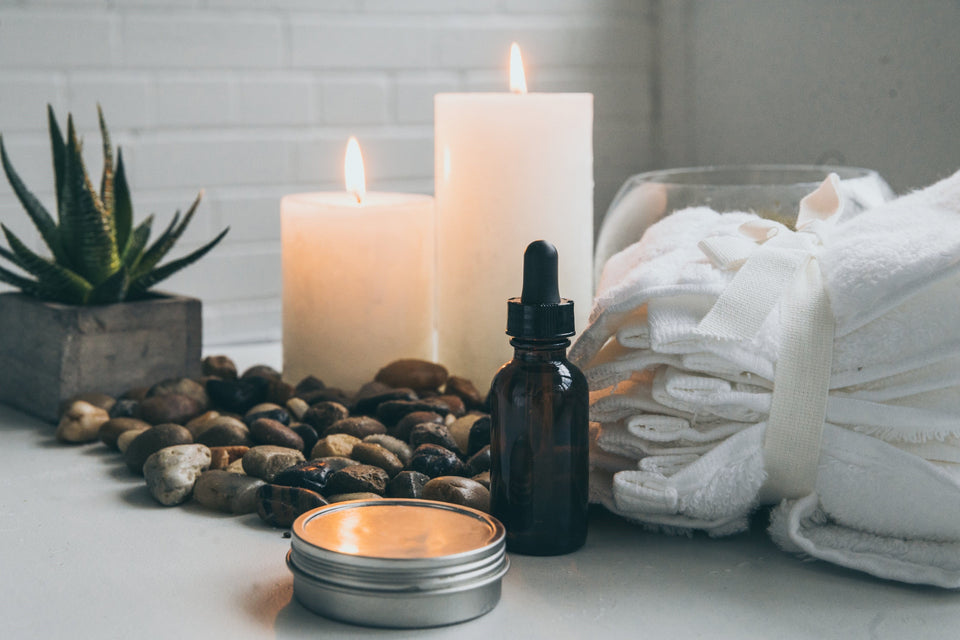 Spa scene with candles burning, a bottle of essential oils, some relaxing stones and white towels.
