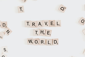 A white scrabble board with the words Travel The World on it.