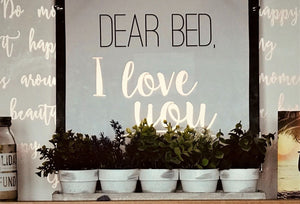 A picture with a black frame and the words Dear Bed. And the words I Love You, written underneath.