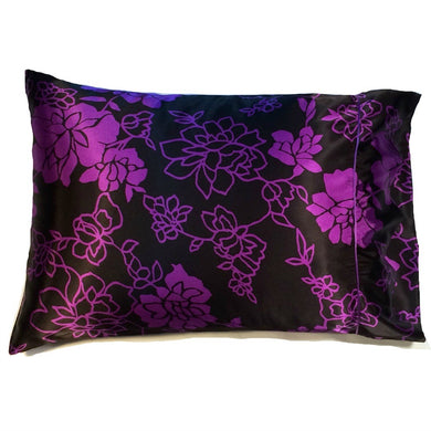 This travel pillow is made from a black with purple flowers  satin print. The pillow feels