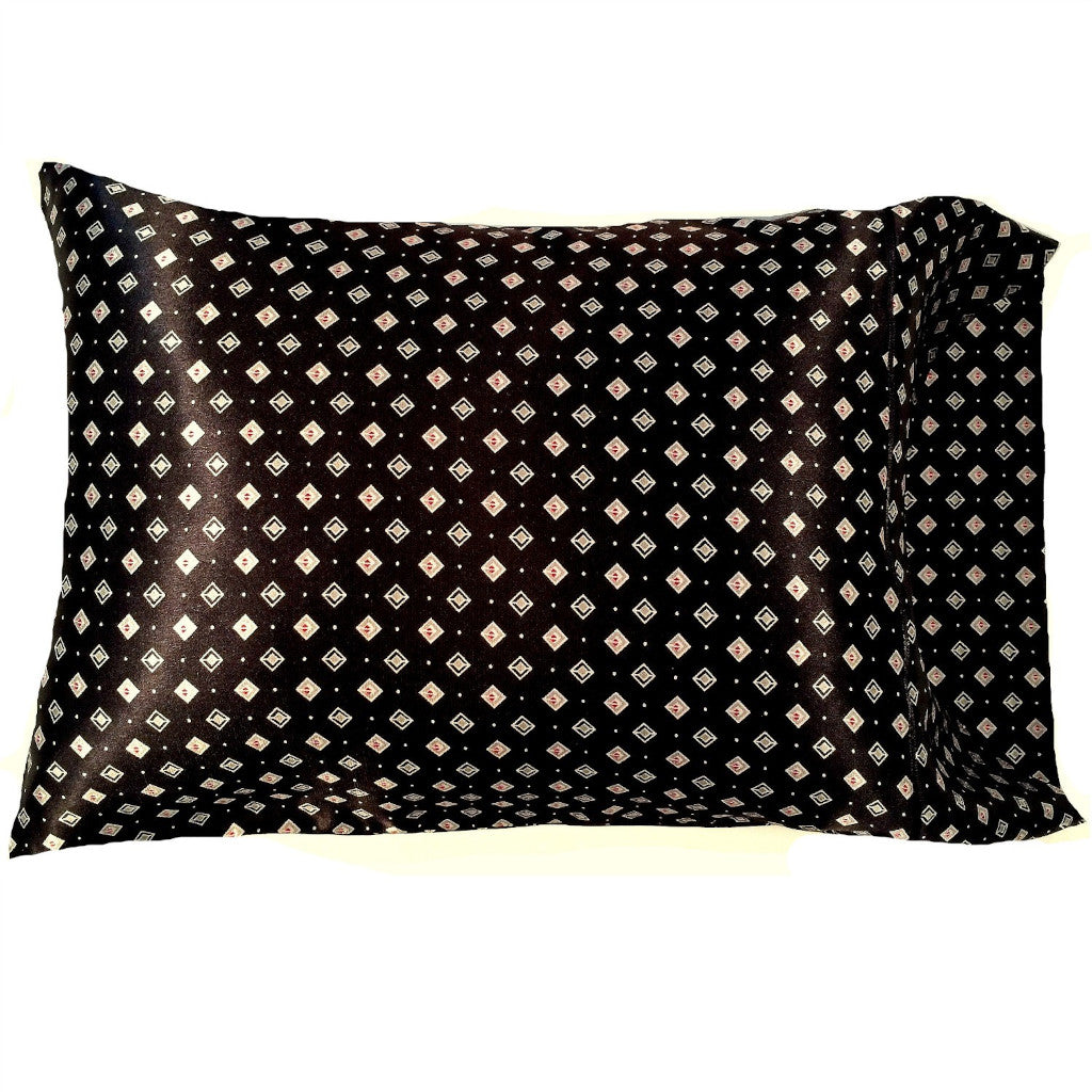 This accent pillow is made from a black with white and red diamonds satin print. The pillow feels