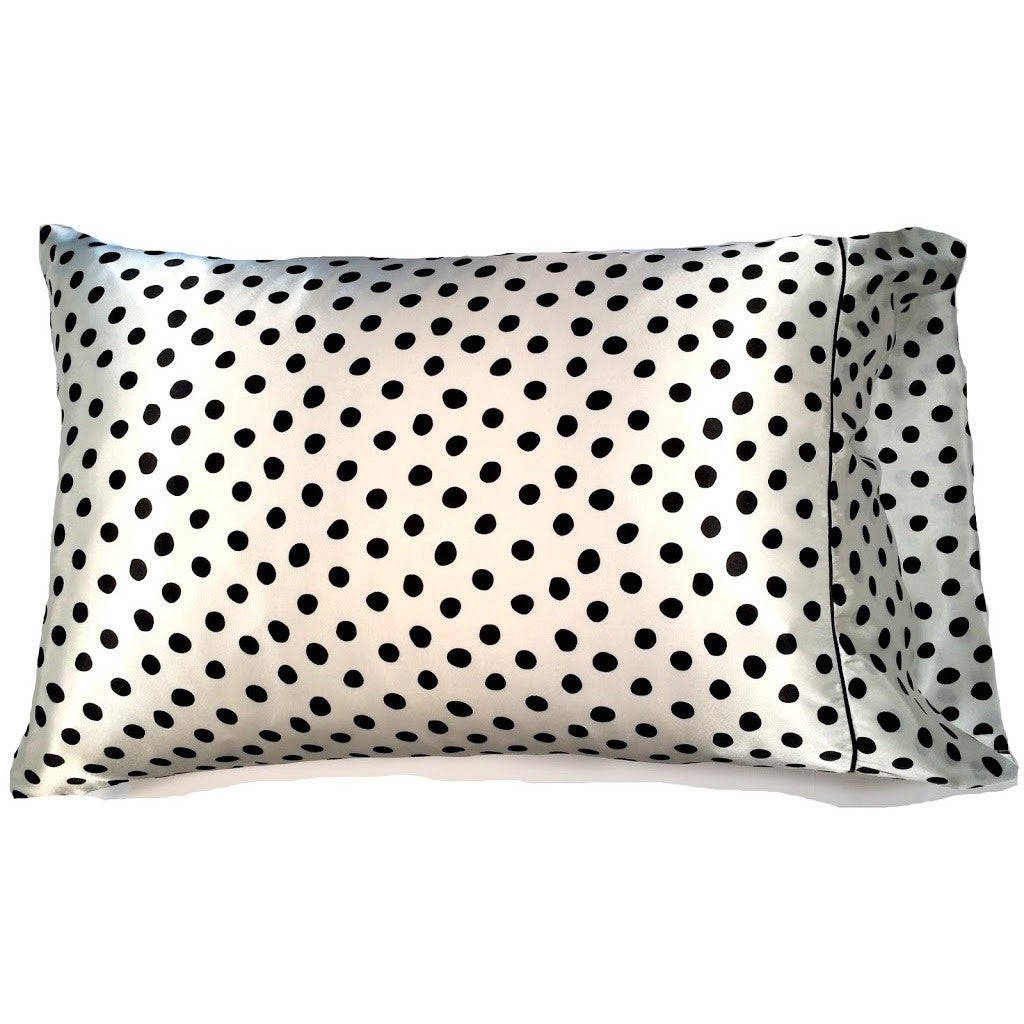 This travel pillow is made from a white with black polka dots satin print. The pillow feels