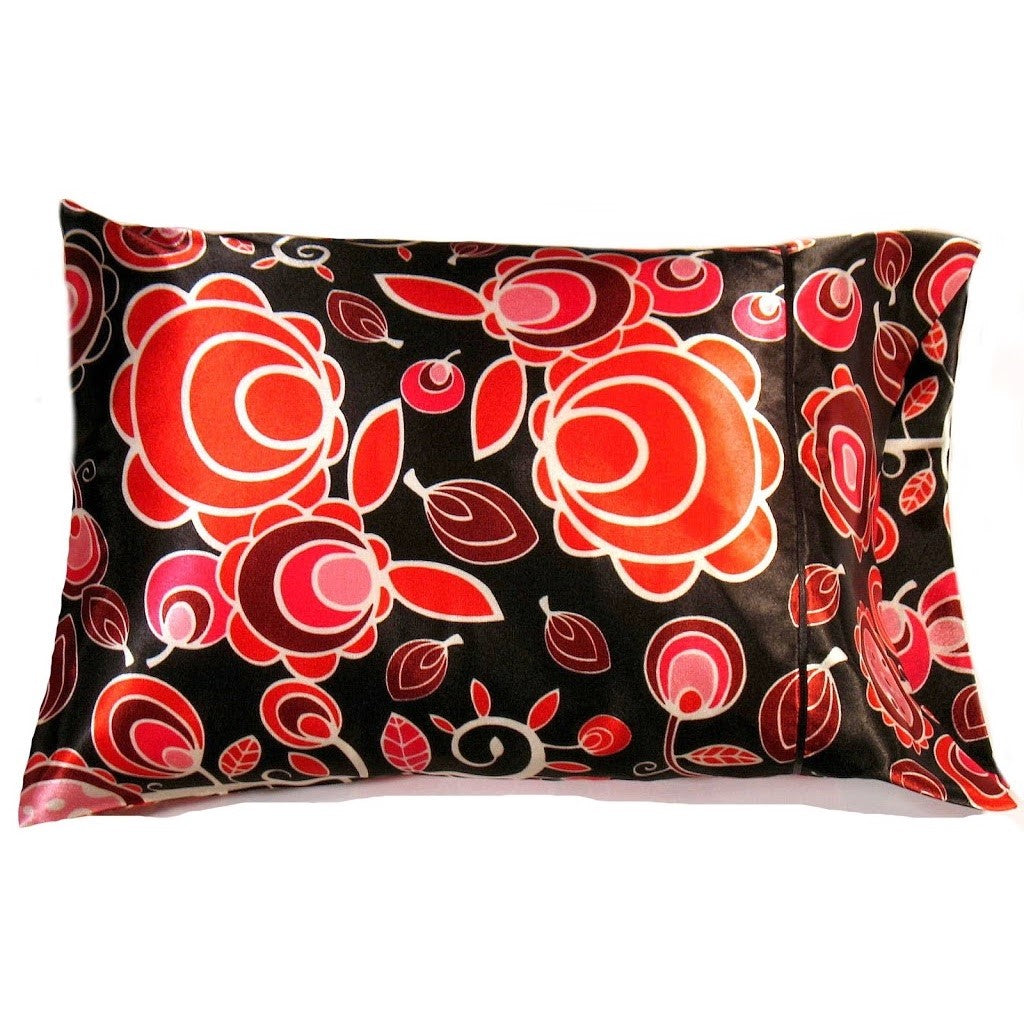 This travel pillow is made from a black and orange  satin print. The pillow feels