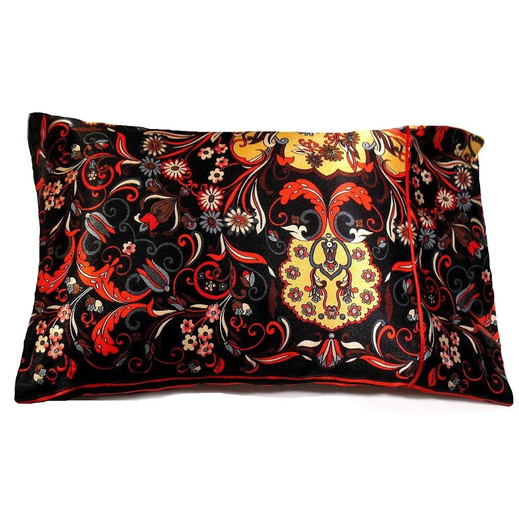 This travel/accent pillow is made from a black, orange and red  satin print. The pillow feels