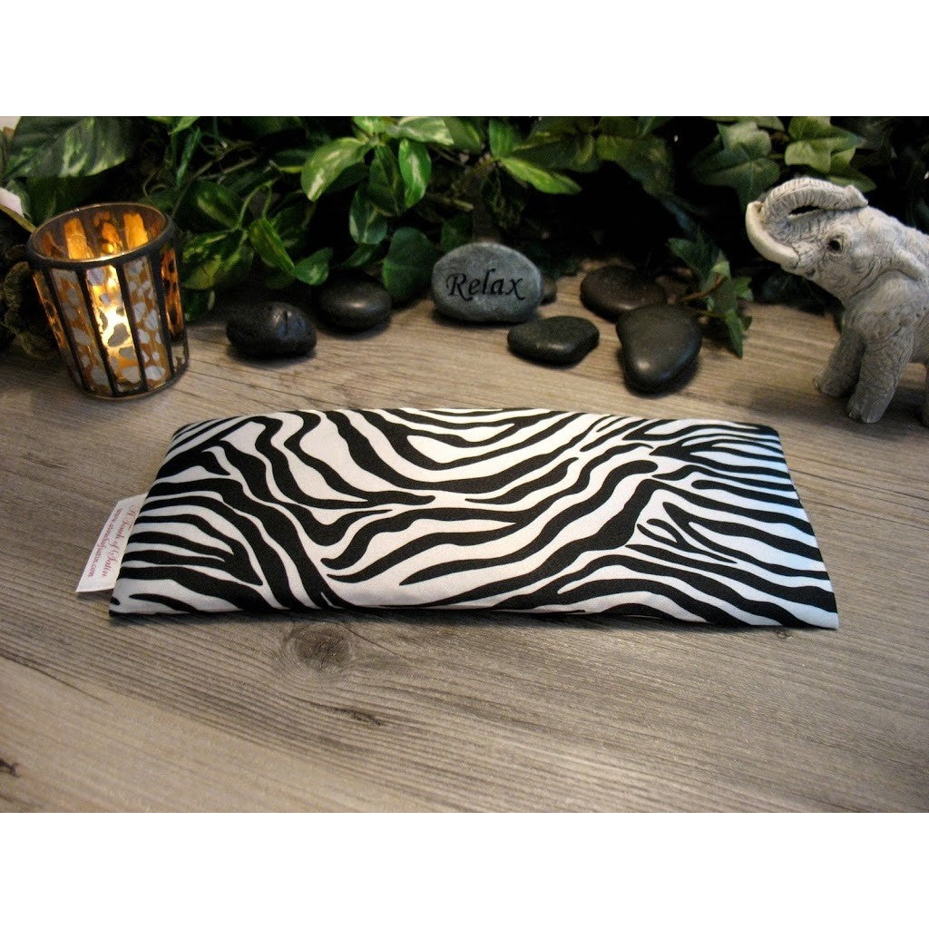 This aromatherapy eye pillow is made with a black and white zebra satin print, filled with organic flaxseed for unscented or choose organic lavender or peppermint for scented.