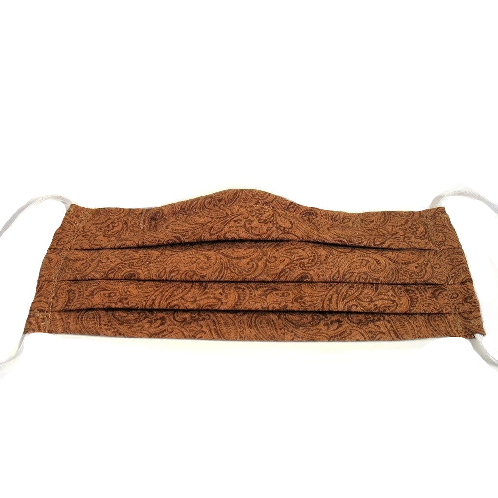 This golden brown paisley print cotton face mask has a pocket in the back for a filter, a nose wire is sewn in for a secure fit and the mask is washable.
