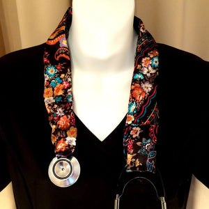 Our stethoscope cover is made from a black, orange and blue charmeuse satin print and is washable. The cover has a Velcro closing to keep it in place.