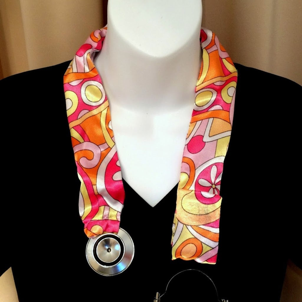 Our stethoscope cover is made from a yellow, pink and orange charmeuse satin print and is washable. The cover has a Velcro closing to keep it in place.