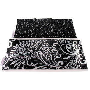 Black and white hot/cold therapy wrap. A washable satin cover with a cotton insert. Three sections filled with organic flaxseed. Microwaveable.