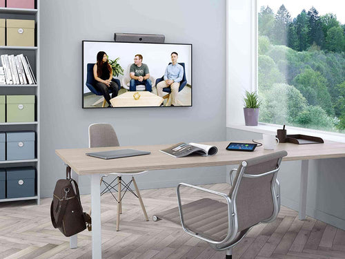 neat bar video sound bar tv display neat pad zoom rooms controller in a modern office for video conference meetings with neatpad zoom room controller, office chair, bookshelf, open book, window with a naural view and backpack on a wooden desk