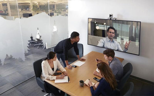 video conference meeting in a small huddle room with a video conference camera in a modern office conference meeting room