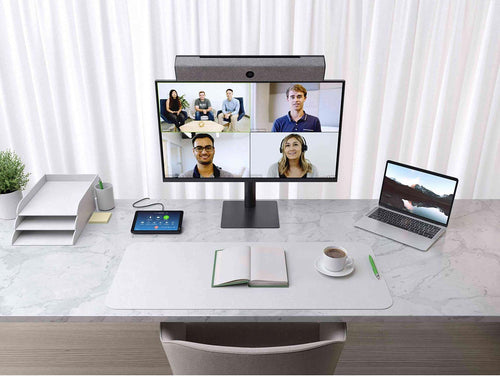 video conference meeting with neatbar video soundbar, neatpad zoom room controller and monitor display laptop and video soundbar with built in conference camera and microphone. Office desk is marble, has organisers, a book, coffee and a pen.