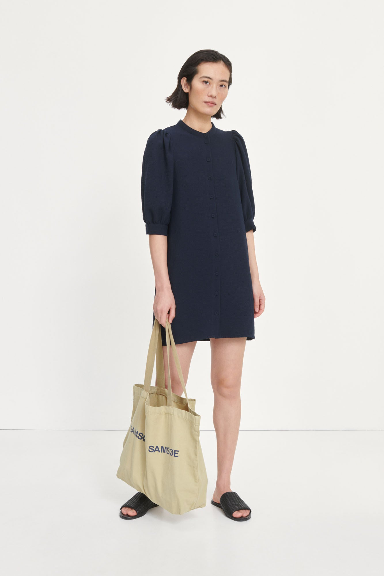 Short shirt dress with deep armholes and elbow length puffed sleeves. Mandarin collar, front button placket, covered buttons. Lightweight lining. Recycled polyester blend fabric with a textured surface. Material: 45% Recycled polyester, 53% Polyester, 2% Elastane