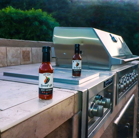 Spice up your grilled hot dogs with Revved Up Spicy Cayenne Hot Sauce. Pictured: hot sauce sitting on the barbecue