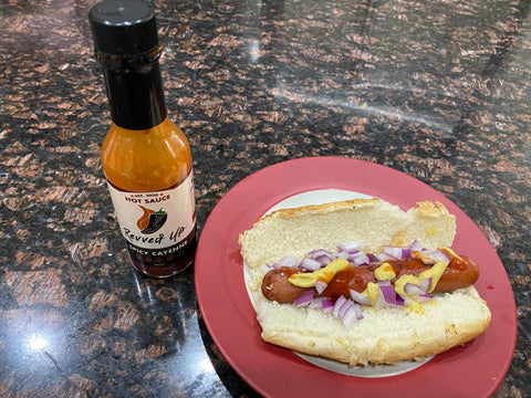 Spice up your hot dog recipe with spicy cayenne. Pictured: grilled hot dog in bun with onion toppings and hot sauce