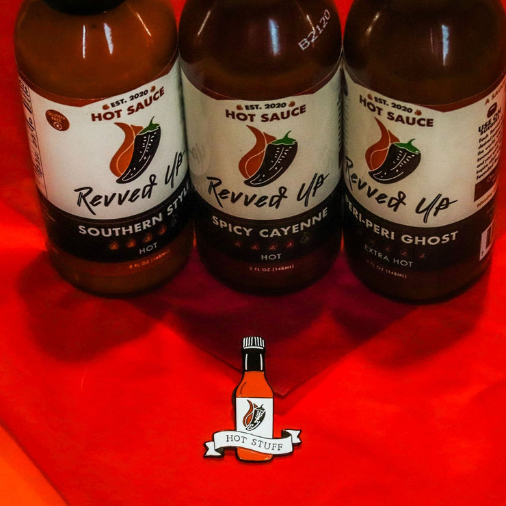 Hot Stuff soft enamel pin with southern style, spicy cayenne, and peri peri ghost hot sauces in the background. background. This hot sauce pin is a spicy way to show off your favorite condiment. Available exclusively here at Revved Up!