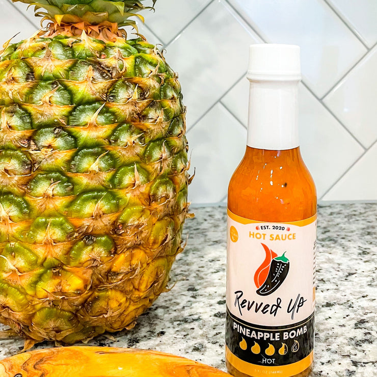 Pineapple Bomb Hot Sauce - | Revved Up. Pineapple Bomb Hot Sauce. Made with real pineapples instead of the artificial stuff typically found in other hot sauces, this zesty mixture gives your boring food new life while giving a tropical sweetness with a medium-high heat that will have your mouth watering for more. Kick up lunches such as chicken sandwiches and burgers or add some flavor to traditional Mexican dishes like burritos and tacos! Pineapple bomb hot sauce in the kitchen next to a pineapple.