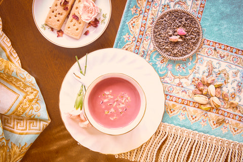 Blush coloured Pink Tea topped with crushed pistachio in a fine bone china cup and shortbread in a plate along with green tea displayed on a beautiful opulent turquoise silk rug and wooden table