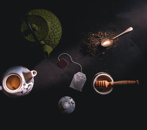 A white teapot and loose leaf tea displayed in a ritual ceremony style