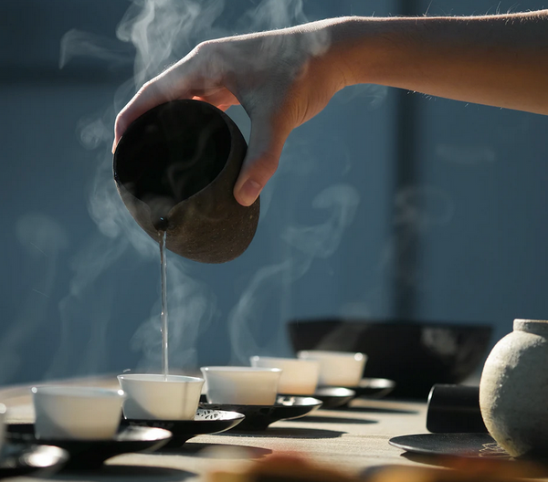 A hand pouring tea into small cups