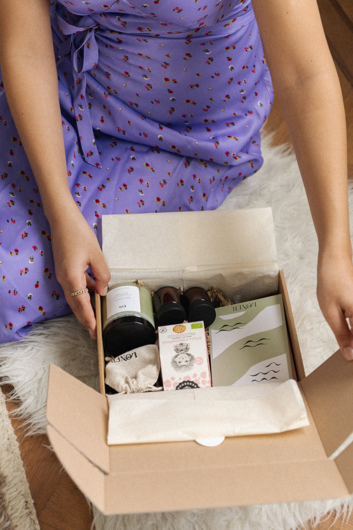 woman is sitting on the floor and opens her loner self-care box
