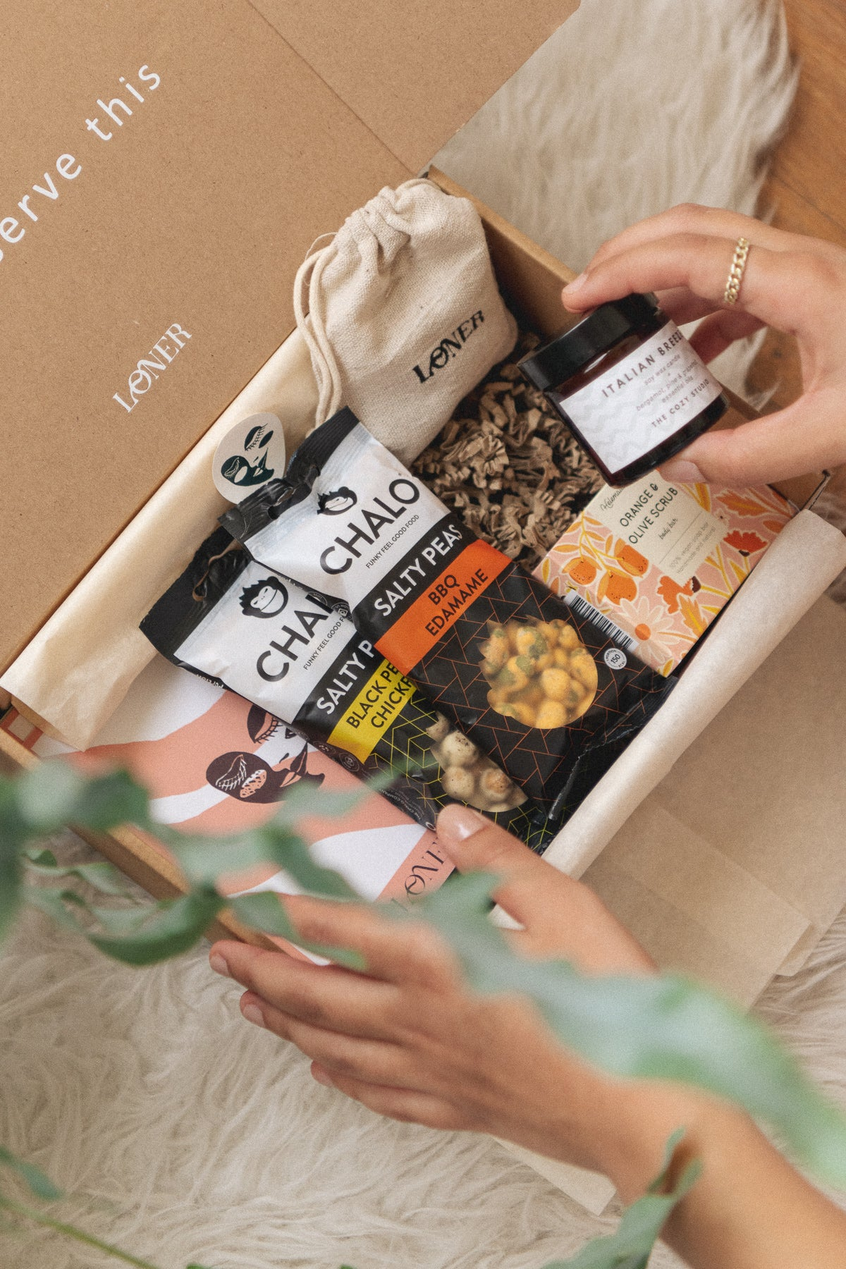 self-care box filled with chalo nuts, a scented candle and  soap bar