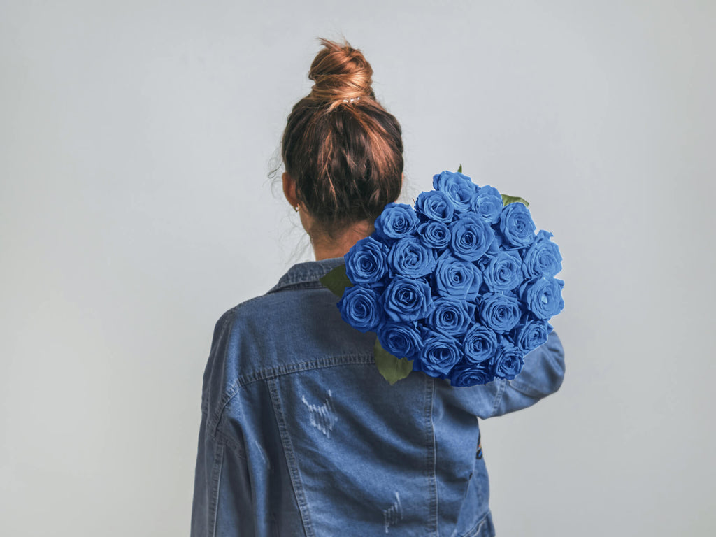 backview of woman carying blue roses