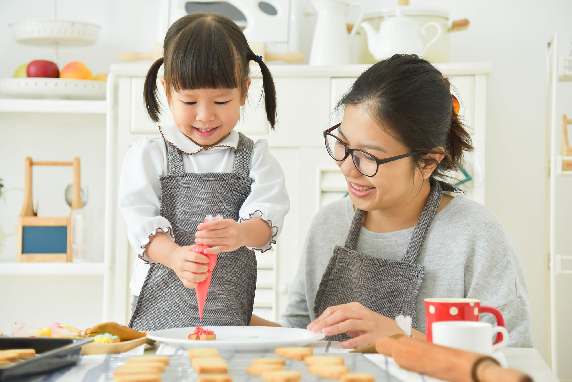 Mom and her daughter are making a mini cookie in the kitchen