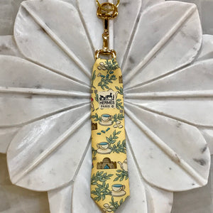 tea cups sage leaves pastel yellow background Hermes designer tie keychain