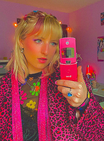 photo of me holding a vintage flip phone, i am wearing a pink cheetah print jacket and i am  looking sassy.