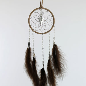 Handmade brown dream catcher with chain dangles detailed with metal feather charms and a metal arrowhead in the middle of the web.