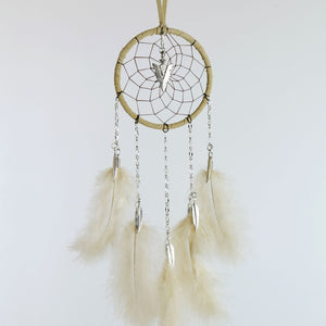 Handmade tan dream catcher with chain dangles detailed with metal feather charms and a metal arrowhead in the middle of the web.