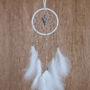 Handmade white dream catcher with chain dangles detailed with metal feather charms and a metal arrowhead in the middle of the web.