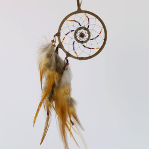 Handmade beaded red canyon dream catcher detailed with a red goldstone semi-precious stone enclosed in a web in the midddle of the web.