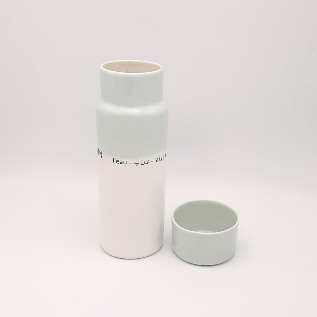 Kaolin - Guðný Magnúsdóttir - H2o WATER KARAFE - are designed in remembrance of the importance of water for all living creatures, the text says water in different languages. WATER - a water bottle in light blue and white glazes. The water bottle comes with a cap.