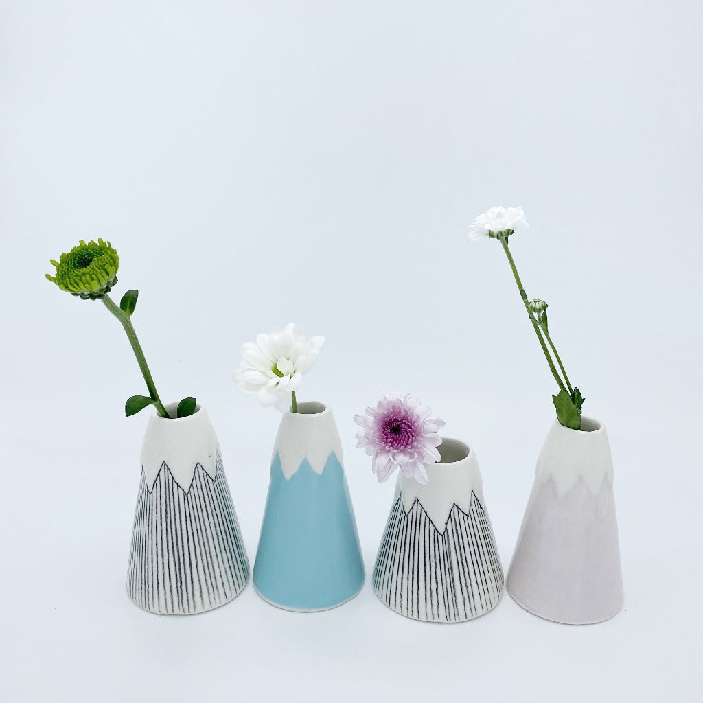 4 volcanoes vases in line, with flowers.