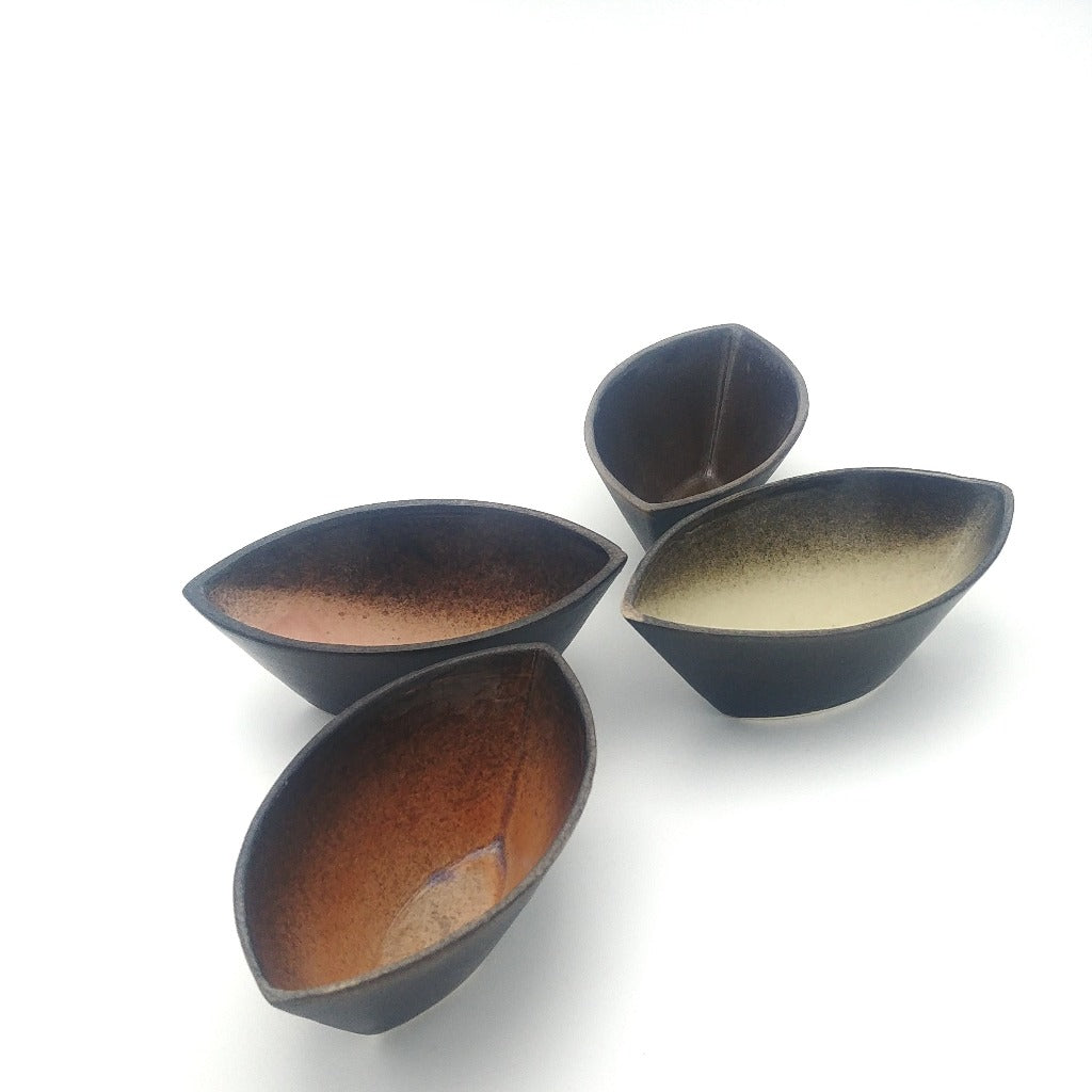 Kaolin-gudnyhaf-boats. Small boats glazed wiidth pink,blue,beige and orange on the inside and black on the outside.