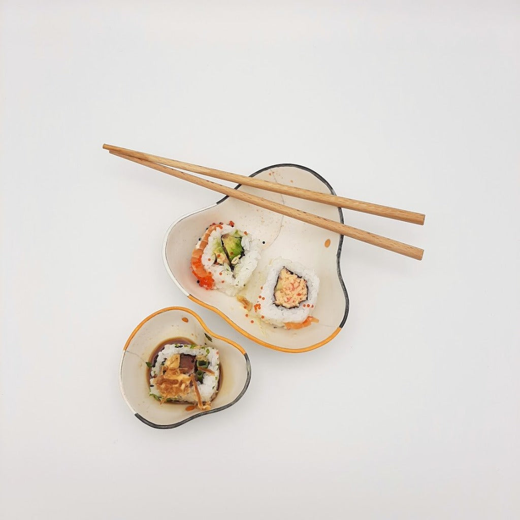Kaolin - Guðný Magnúsdóttir - Sushi bowl, a set of two porcelain designed for three Sushi bites and the small one for the soya. Soft triangle form with white glaze, black and orange decoration.