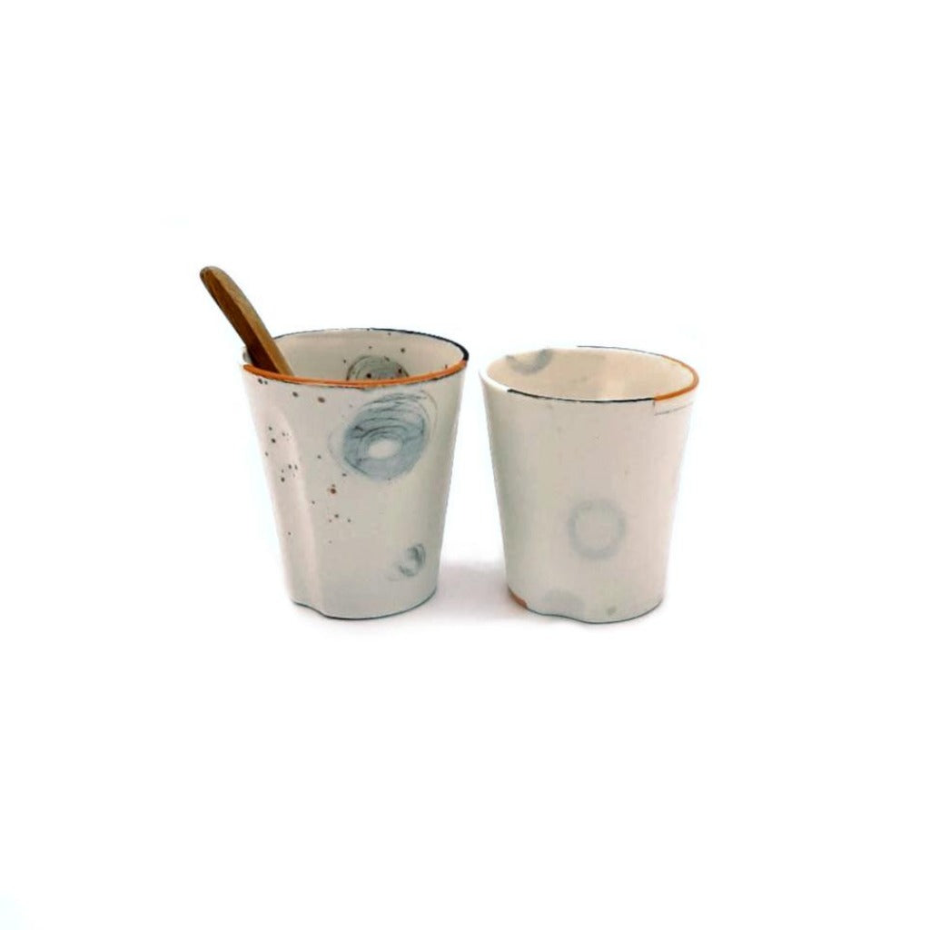 Kaolin - Guðný Magnúsdóttir - The Tea glasses or Espresso cups have each their own character in form and decoration. They are in white porcelain, hand painted individually  with orange and black lines on the edge and come in a set of two.