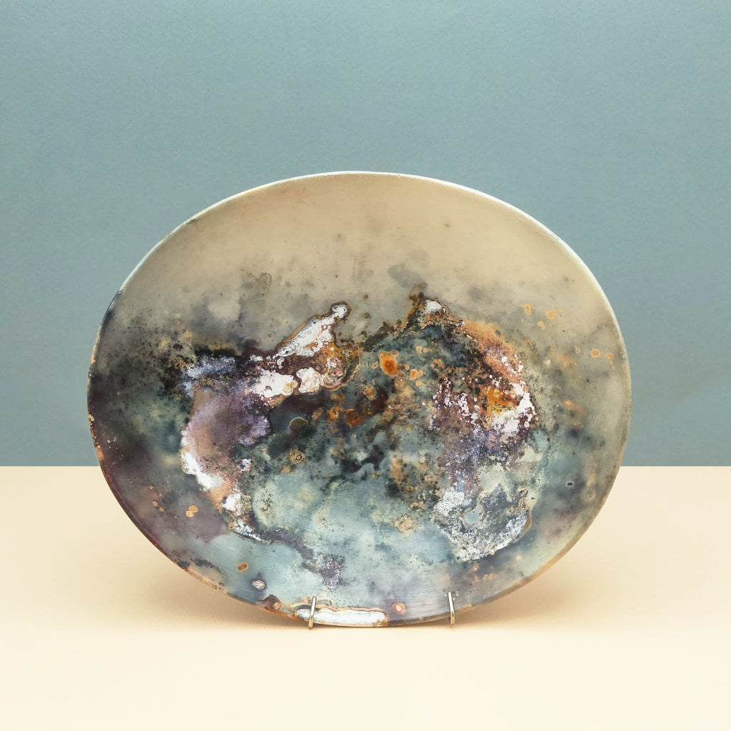 Kaolin - Kvalka - Shallow smoke fired handmade ceramic bowl. Displayed on a stand . The colors are blue, violet, burgundy, white, orange and grey.