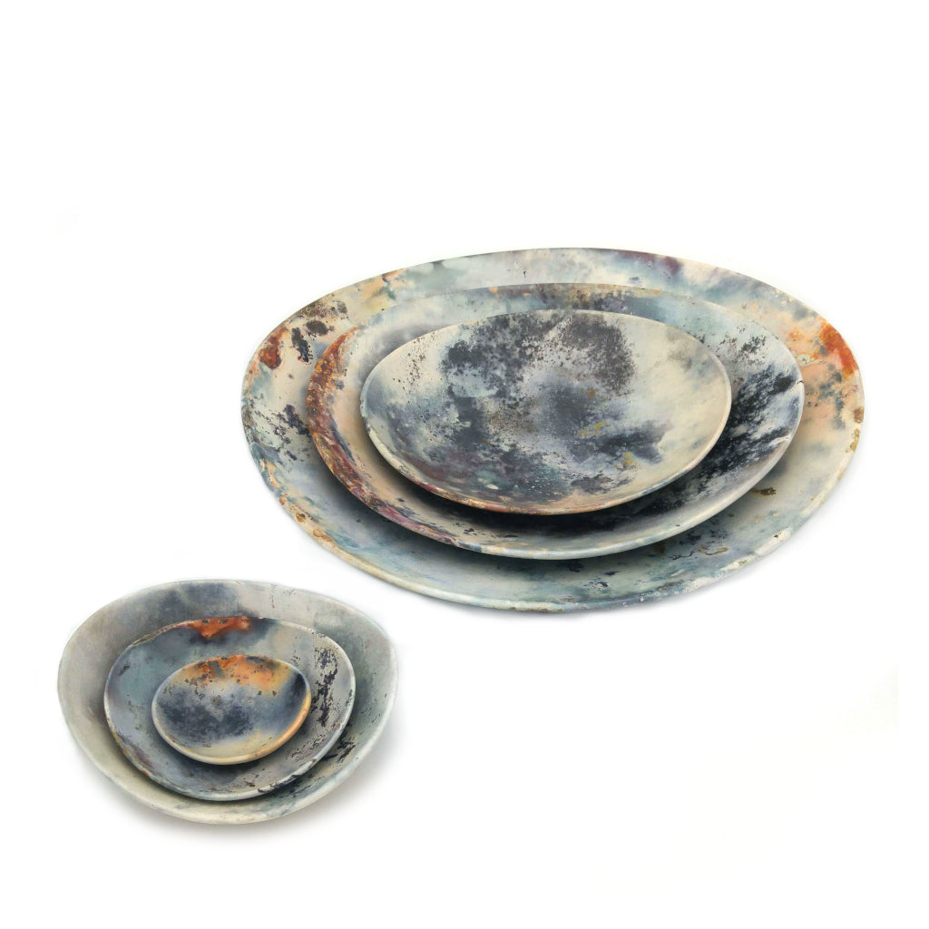 Kaolin - Kvalka - Six nestled smoke-fired handmade ceramic bowls. Displayed in two groups nestled together. Three smallest and three bigger. View from above. Multicolored.