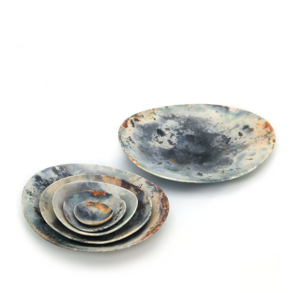 Kaolin - Kvalka - Six nestled smoke-fired handmade ceramic bowls. Displayed in two groups, Five of the smallest nestled together and the biggest one stands alone. View from above. Multicolored.