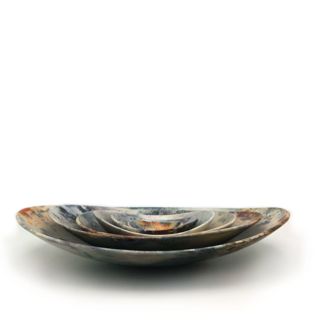 Kaolin - Kvalka - Six nestled smoke-fired handmade ceramic bowls. Displayed nestled together. Side view. Multicolored