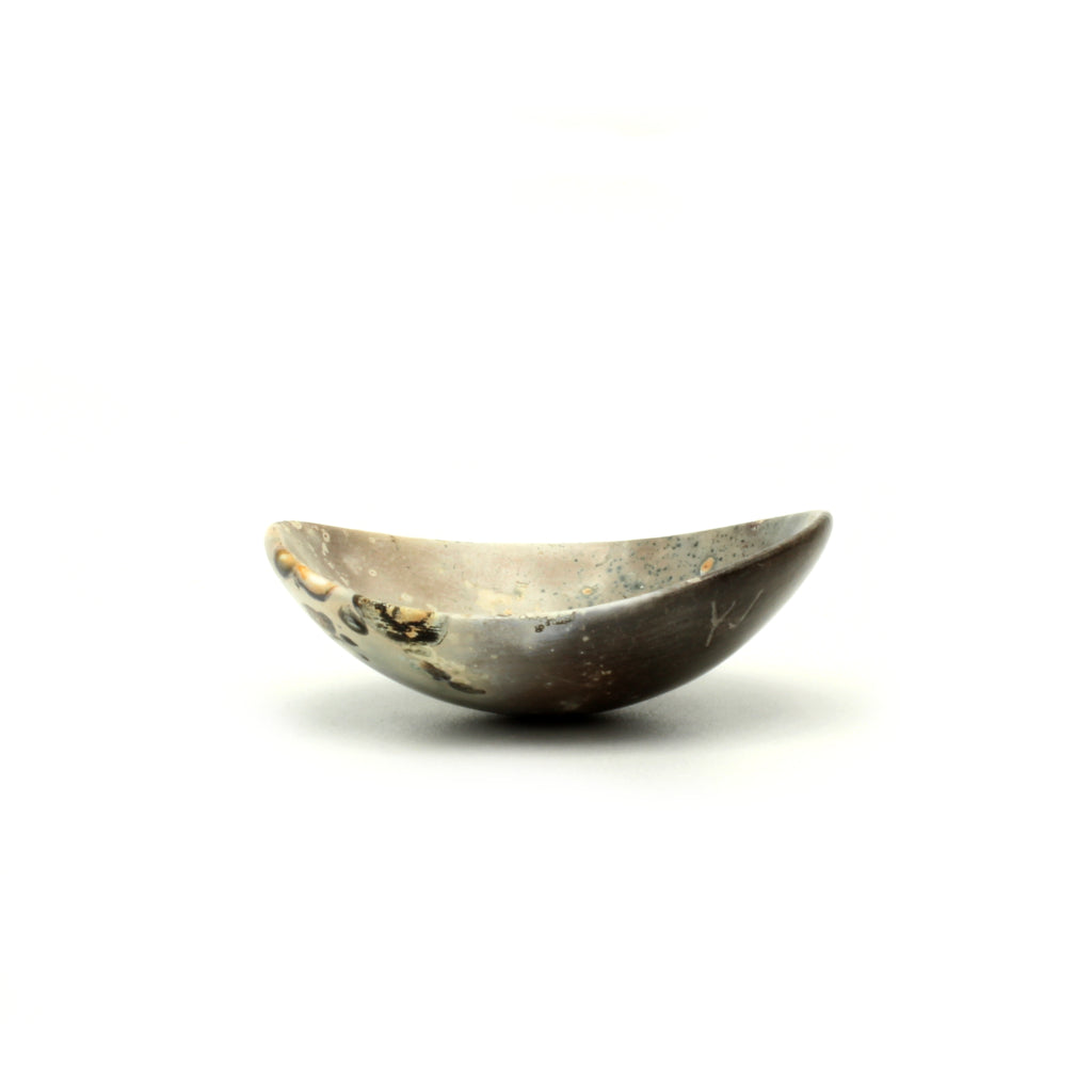 Kaolin - Kvalka -  Small and shallow smoke fired handmade ceramic bowl. The shape of the bowl is like the bottom of a sphere. The colors are brown, white and black with green dots and black and orange spots.