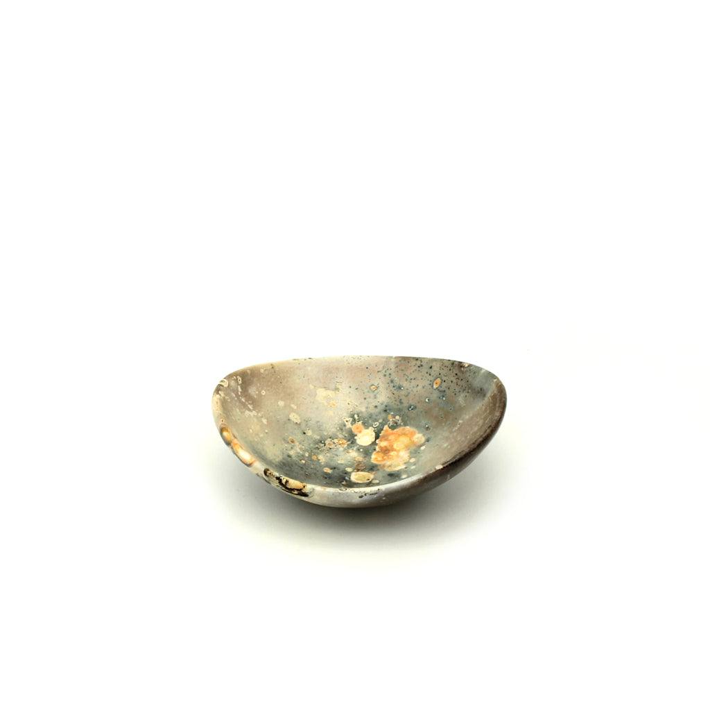 Kaolin - Kvalka -  Small and shallow smoke fired handmade ceramic bowl. View from one side. The colors inside the bowl are brown, white and grey with small green dots and orange splashes.