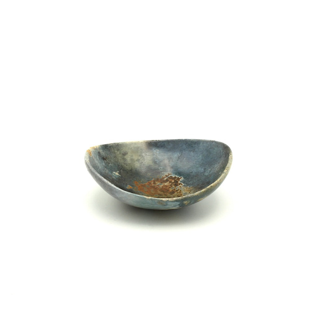 Kaolin - Kvalka -  Small and shallow smoke fired handmade ceramic bowl. View from one side. The colors inside the bowl are hues of blue and grey with splatter of rusty colors in the center.