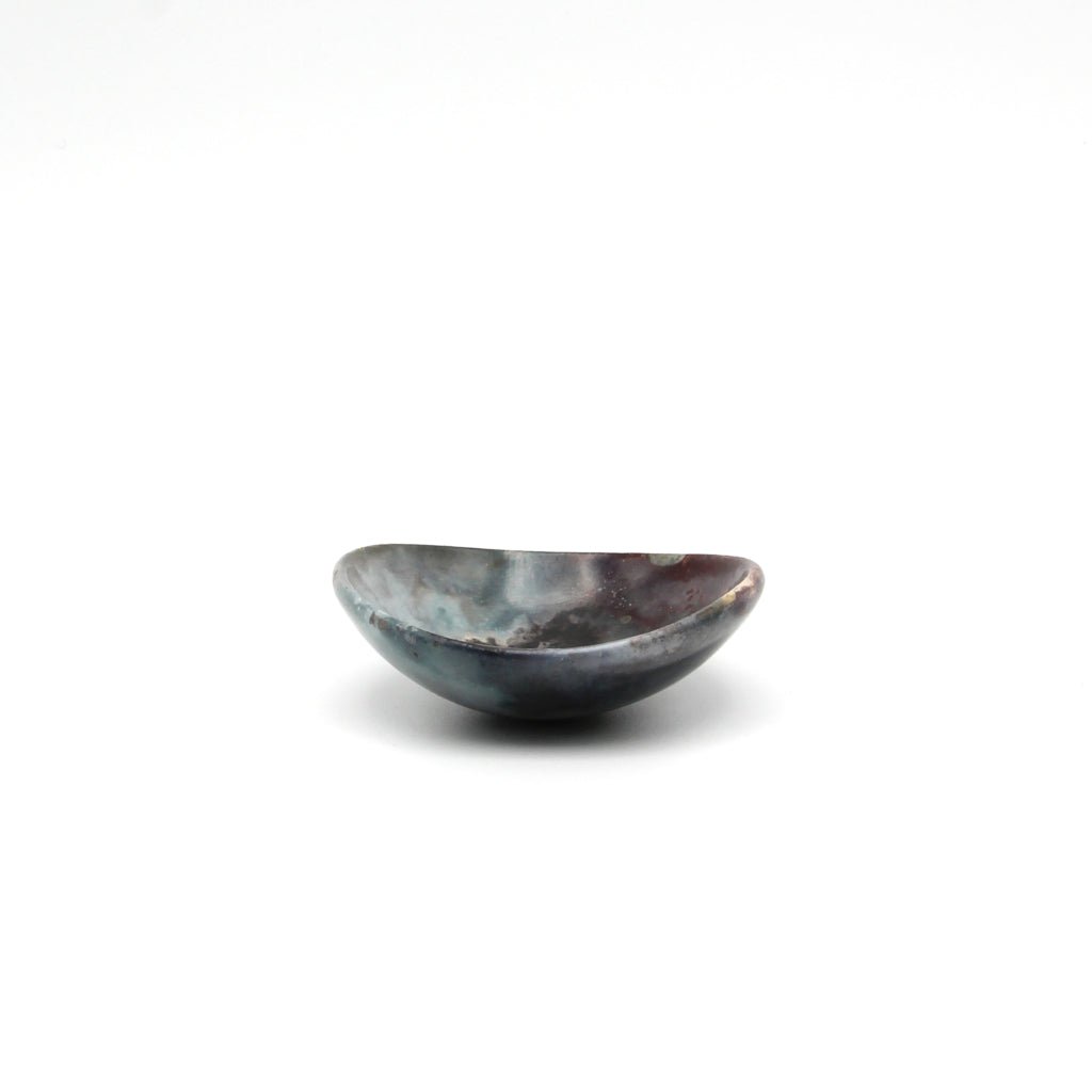 Kaolin - Kvalka -  Small and shallow smoke fired handmade ceramic bowl. The shape of the bowl is like the bottom of a sphere. The colors are hues of blue, grey, black and burgundy.